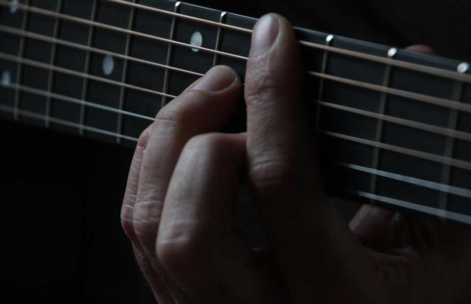 guitarist-playing-a-chord-on-fredboard